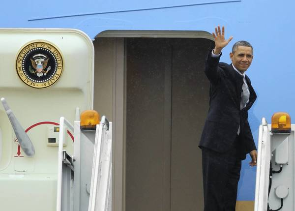 After a visit to Argonne National Laboratory, President Barack Obama waves goodbye as he boards Air Force One at O'Hare International Airport.