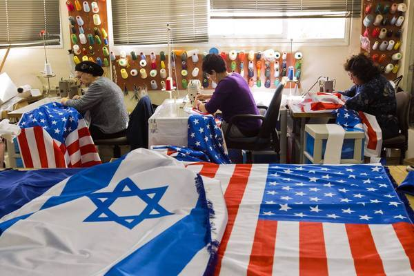 Workers in the town of Kfar Saba ready U.S. and Israeli flags in preparation for President Obama's visit to Israel and the West Bank.