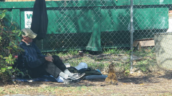 This homeless man and a cat were right outside the parking garage for the awards ceremony