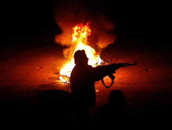 A Syrian rebel is silhouetted against a flaming tire while firing at an army checkpoint in a suburb of Damascus.