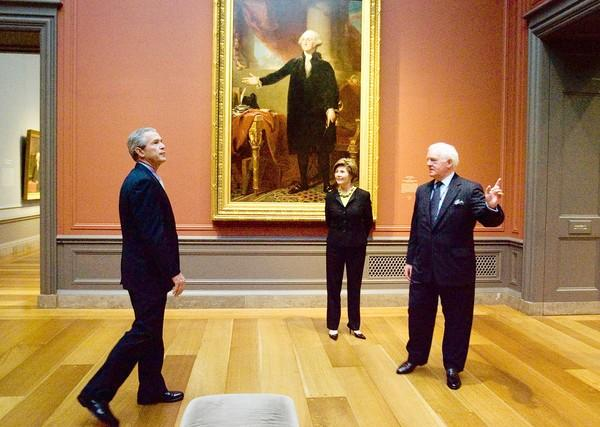 "The National Gallery of Art's strong suit is not modern art. Here, then-President George W. Bush and his wife Laura receive a tour of a Gilbert Stuart exhibition at the NGA from Director Earl ""Rusty"" Powell, formerly of LACMA, in 2005."