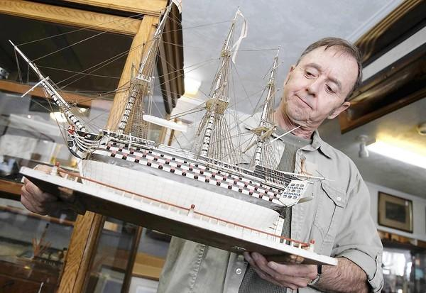 Joe Vallejo holds a French Prisoner of War model ship circa 1790, one of his favorite and most rare items he is letting go at the Vallejo Gallery, which closes this weekend after being in business for 41 years in Newport Beach.
