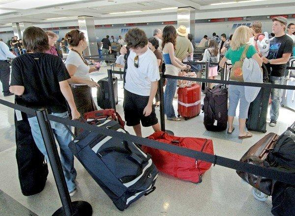 Travelers roll luggage through an airport.