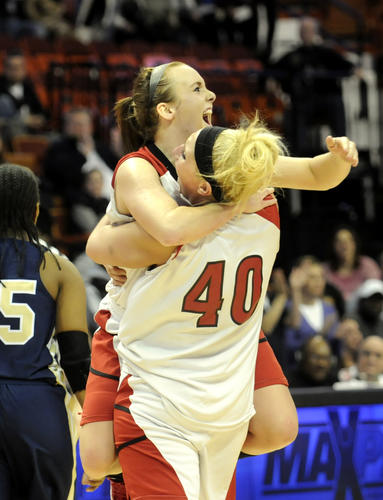 Kelly Flanigan jumps into the arms of teammate Lindsay Langenauer at the buzzer as Cromwell won the Class M championship. Cromwell won, 42-28.
