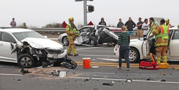 Firefighters assess the scene where three cars were involved in a crash at the intersection of East Coast Highway and Newport Coast Drive.