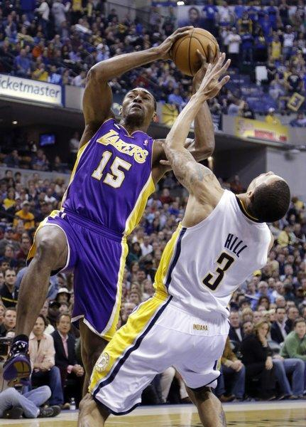 Pacers guard George Hill (3) takes a charge from Lakers forward Metta World Peace during the first half Friday night.