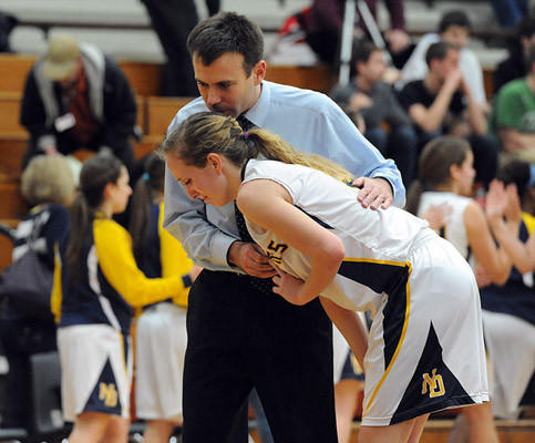 Notre Dame's head basketball coach Josh Kopp (back) consoles Lexi McGivern (front) after losing to Saint Basil Academy 45 - 42 in the PIAA 2A girls quarterfinal basketball tournament Friday night.