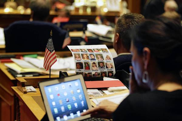 Colorado State Sen. Angela Giron works at a desk near her poster bearing the faces and names of the young victims of the Sandy Hook School massacre during a recent debate period for one of several gun control bills before Colorado lawmakers.