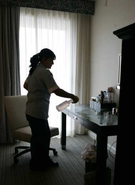 Housekeeper Marina Ortiz sprays cleaner-disinfectant on desk inside a Sheraton hotel room.