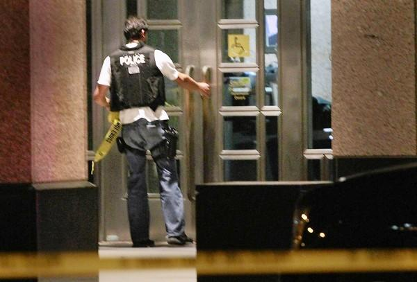 A police officer enters the federal building in Long Beach after the ICE shootings in February 2012.