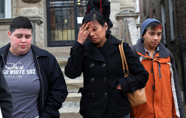 Cecilia Garcia, center, mother of Joaquin Garcia, leaves the home belonging to the family of Fabian Torres Saturday afternoon. Torres and Garica were killed after being struck by a vehicle driving in the wrong direction on Lake Shore Drive Friday morning.  The Garcia family was trying to meet with the family of Torres, but were unsuccessful.