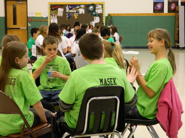 Sara Fletcher, 10, of Hagerstown, left, Tommy Inman, 10, of Martinsburg, W.Va., second from left, and Bekah Jonhnson, 10, of Martinsburg, W.Va., right, brainstorm an answer with Homeschool Hurricane team members Saturday during Washington County Free Library's Battle of the Books at Eastern Elementary School in Hagerstown.