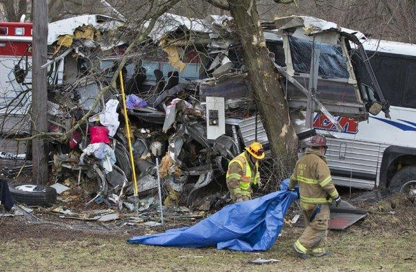 Rescue workers remove a tarp after a bus crash on the Pennsylvania Turnpike. Lacrosse players from Seton Hill University in Greensburg, Pa., were among 23 people aboard. A coach and the bus driver were killed.