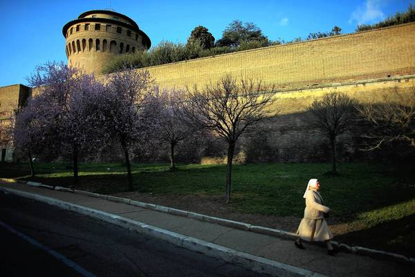 A nun walks along the outer wall of Vatican City, which will soon be home to two popes: Francis and Benedict XVI, who has taken the title of pope emeritus.