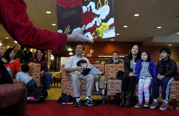 "Children and adults listen to the reading of ""The Giant Glowing Dragon"" during the Mandarin story hour at the Crowell Public Library in San Marino."
