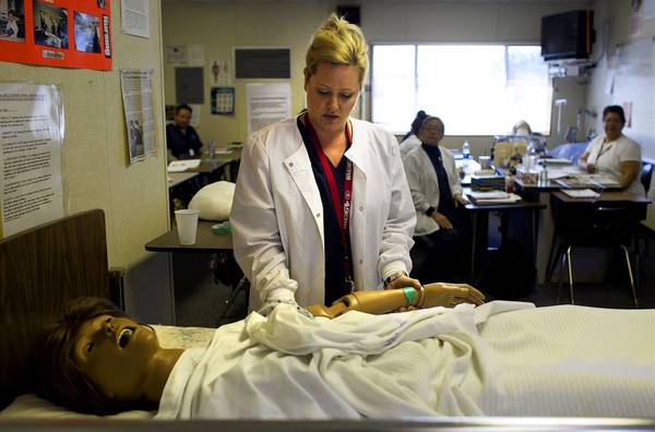 Tiffany Bonham uses a dummy patient during a certified nursing assistant class at Azusa Adult School, which will close this year.
