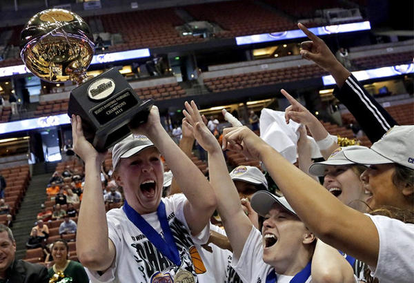Molly Schlemer holds the trophy as she and teammates celebrate their 63-49 win over Pacific.