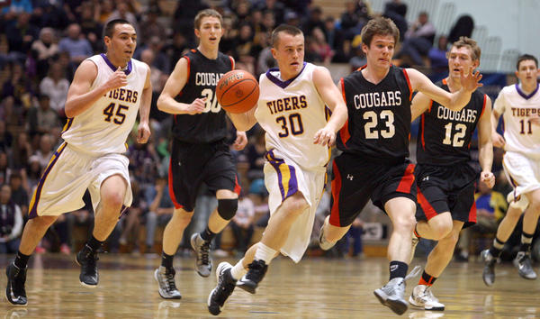White River's Wyatt Krogman, center, pushes the ball up the floor ahead of teammate Matthew Gillen (45) and Viborg-Hurley's Andrew Hora (30), Trevor Jacobsen (23) and Tyler Gerdes (12) during the championship game Saturday night at the South Dakota Class B Basketball Tournament at Wachs Arena. At far right for White River is Joe Cameron. photo by john davis taken 3/16/2013