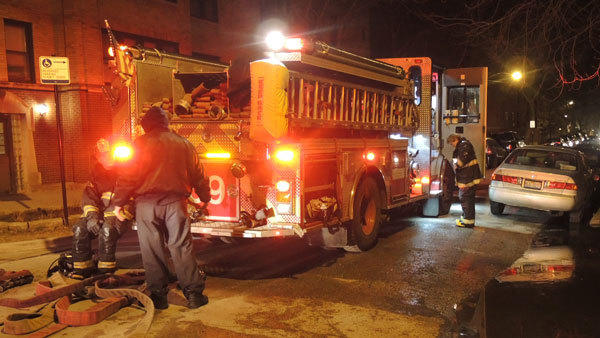 Firefighters outside an apartment that caught fire in the 4800 block of North Lawndale Avenue.