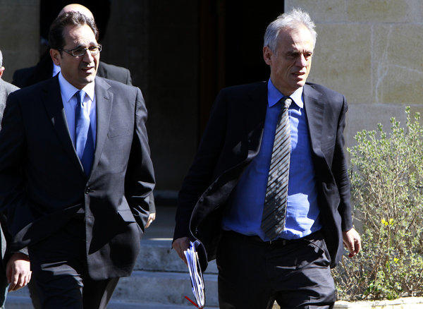 Cyprus' Financial Minister Michalis Saris, right, leaves a meeting Sunday with president Nicos Anastasiades at the presidential palace in Nicosia, Cyprus. Cyprus' parliament had postponed debate and a vote on a controversial levy on all bank deposits that the cash-strapped country's creditors demanded in exchange for a bailout.