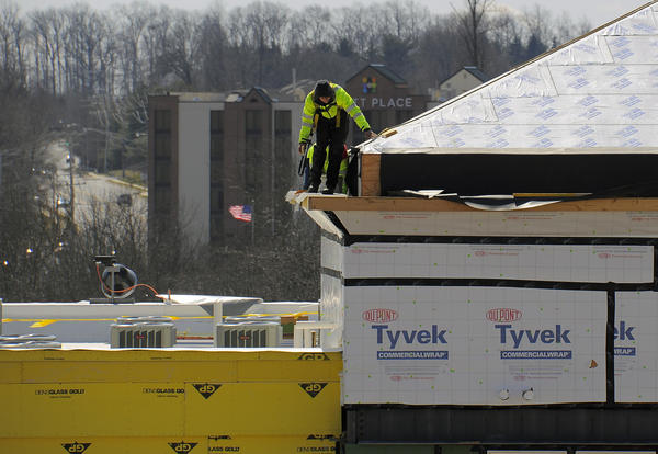 Owings Mills Boulevard can be seen at left as two construction workers brave a biting March wind while working on the roof at Metro Centre, a mixed-use project at the Owings Mills Metro station. the first piece of the project, a county library branch, will open this month.