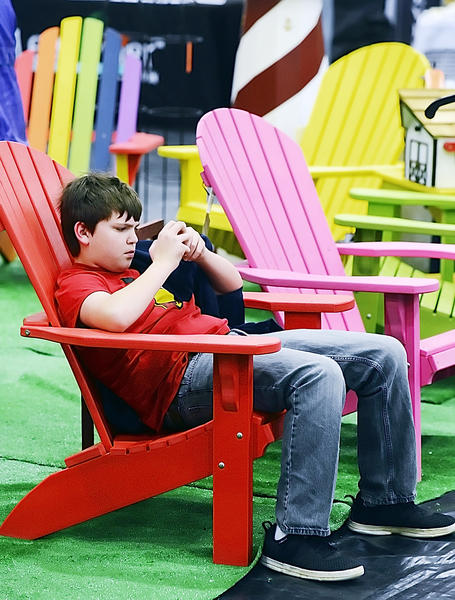 Geoffrey Souza, 12, of Hagerstown, found the perfect spot to play a game on his iPod while he waits for his parents to walk around at the Hagerstown Community College Alumni Association's 19th annual Flower & Garden Show on Sunday.  The lawn chairs were at the Things Outdoors booth.