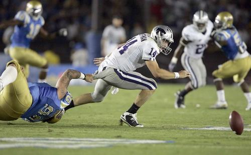 Kansas State quarterback Carson Coffman fumbles as he pulled down by UCLA's Jerzy Siewierski in the second quarter Saturday.