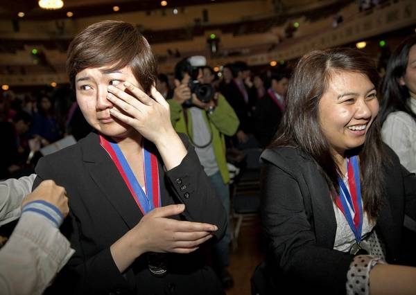 Jenny Baek, left, and teammate Beatrice Dimaunahan of Granada Hills Charter have different reactions to their team's win.