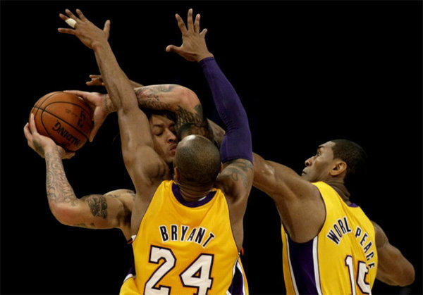 Lakers' Kobe Bryant and Metta World Peace apply pressure to Phoenix Suns forward Michael Beasley.