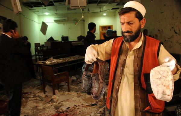 Pakistani rescue workers inspect the scene of a suicide bomb blast targeting a courtroom in Peshawar, Pakistan.