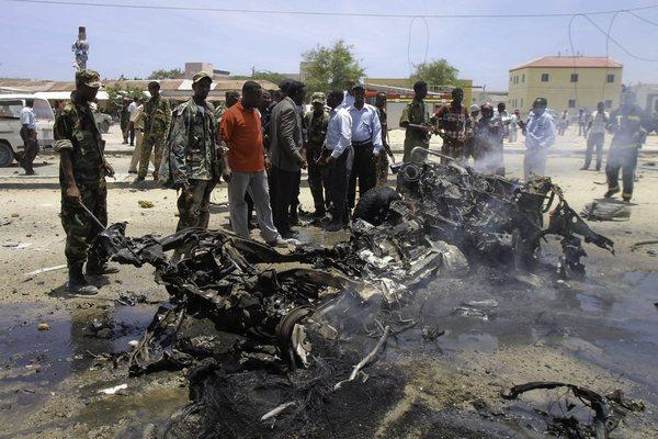 Security officers gather at the scene of a suicide car bomb explosion near the presidential palace in Mogadishu, Somalia.