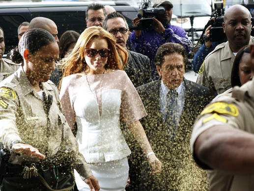 Actress Lindsay Lohan is showered with gold glitter as she walks with her attorney, Mark Heller, into Los Angeles County Superior Court. She has been charged with three misdemeanor counts stemming from a car crash in 2012 on Pacific Coast Highway.
