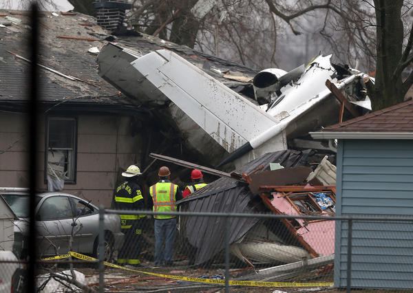 Emergency personnel look at the wreckage of a small jet that crashed into houses in South Bend.