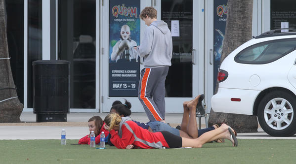 Students relax outside of the UCF arena Monday, March 18, 2013 after a person was found dead on campus and explosives and guns were found.