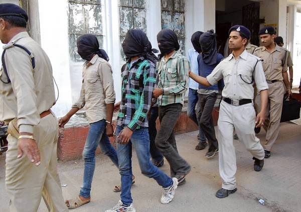 Police escort men accused of a gang rape to a court in Datia district in the central Indian state of Madhya Pradesh. Police have arrested six men accused of the gang-rape of a Swiss tourist who was camping with her husband in an Indian forest in the central state of Madhya Pradesh.