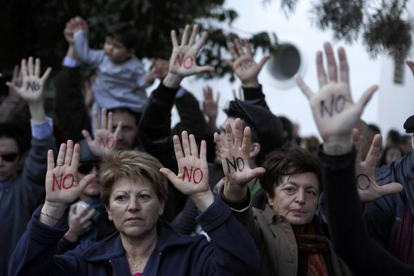 "Cypriots show their palms reading ""No"" during a protest against an EU bailout deal outside the parliament in Nicosia. Cyprus's parliament has postponed until March 19 a session to vote on the bailout deal that slaps a levy on all Cypriot bank savings, as negotiators scrambled to soften the blow for small deposit holders."