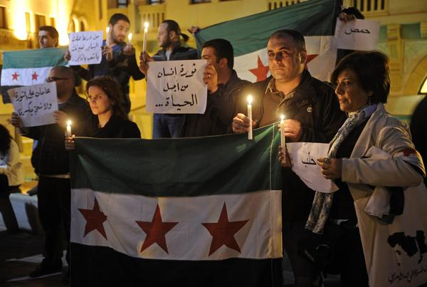 Lebanese activists in Beirut light candles as they hold Syrian revolutionary flags during a rally to mark the second anniversary of the revolt against the regime of Syrian President Bashar Assad.