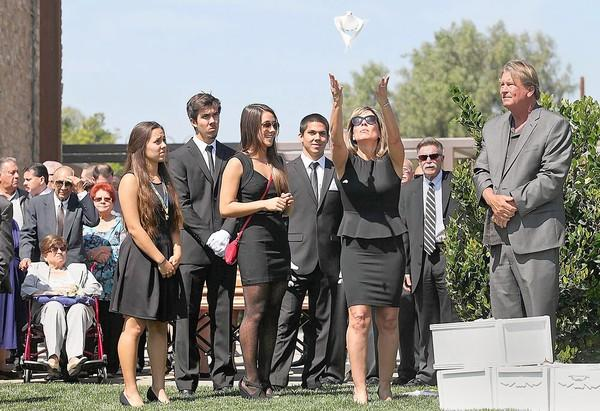 Desiree Delgadillo, third from right, releases a single dove as her children, standing from left, Ivy, Quinton, Sierra and Noah look on during a memorial service for her ex-husband, Costa Mesa Police Det. MIke Delgadillo, at Saint Thomas More Catholic Parish on Friday.