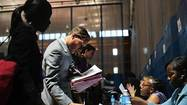 Job seekers speak to recruiters at a job fair sponsored by New York Department of Labor