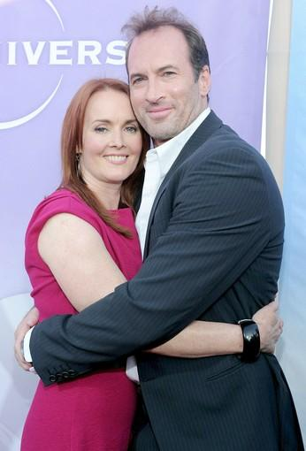 "Laura Innes, who plays the leader of a group of detainees in NBC's ""The Event,"" poses with actor Scott Patterson on the red carpet."