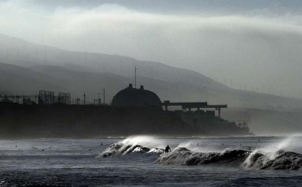 Surfers ride the waves at Lower Trestles near San Clemente as the darkened San Onofre nuclear plant looms in the distance.