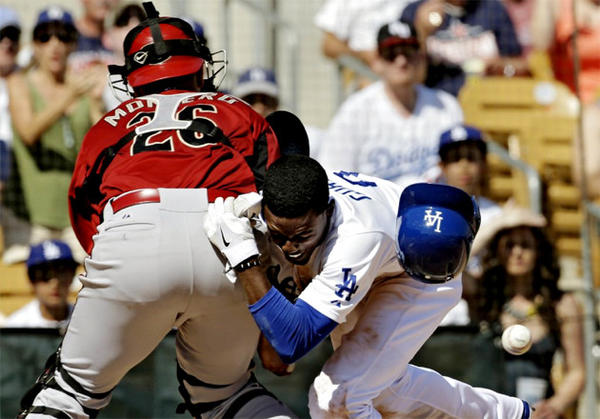 The Dodgers' Dee Gordon knocks the ball away from Arizona Diamondbacks catcher Miguel Montero (26) to score on a single by Carl Crawford.