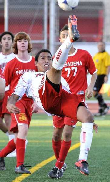 Burroughs' Manny Celio leans and jumps to attempt a bicycle kick shot towards goal against Pasadena in the second half in a Pacific League boys soccer match at Burroughs High School in Burbank on Monday, January 28, 2013. Pasadena won the match 3-1.