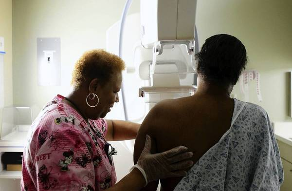 A woman has a routine mammogram in Chicago. Results of a Danish study about the long-term psychological effects of false-positive scares raise new questions about how often women need to have such cancer screenings.