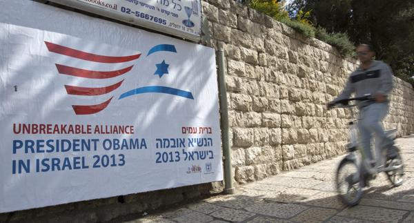 A cyclist passes a billboard near the hotel where President Obama will be staying in Jerusalem, when he arrives on March 20 for his two-day visit.