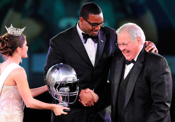 Former New York Giants defensive tackle and Ed Block Courage Award recipient Chris Canty, center, who was recently signed by the Baltimore Ravens, talks to emcee and former Baltimore Colt Tom Matte, right, as Miss Maryland 2012Joanna Guy, left, presents Canty's trophy during the NFL's Ed Block Courage Awards gala at Martin's West in Baltimore.