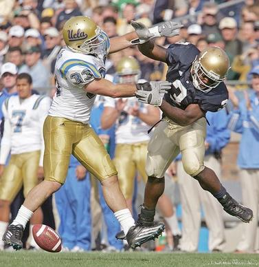 UCLA linebacker Christian Taylor, left, makes sure Notre Dame's Darius Walker doesn't hold on to a pass as the ball falls incomplete dur