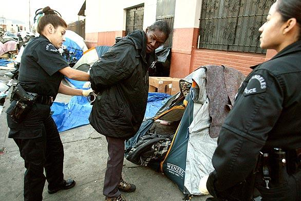 A homeless woman is arrested for sleeping on a public sidewalk during an early morning sweep of L.A.'s skid row on Nov. 20, 2002, as the LAPD launched a campaign by new chief William J. Bratton to clean up the area.
