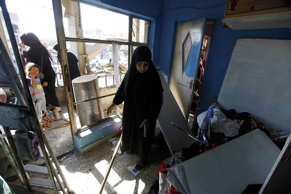 A woman stands inside her destroyed house after a car bomb attack in the Al-Mashtal district in Baghdad. A series of coordinated car bombs and blasts hit Shi'ite districts across Baghdad and south of the Iraqi capital, killing at least 25 people on the tenth anniversary of the U.S.-led invasion.