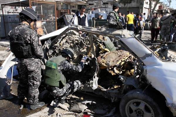 Iraqi policemen examine the remains of a car bomb in Baghdad's Sadr City March 19, 2013. A series of coordinated car bombs and blasts hit Shi'ite districts across Baghdad and south of the Iraqi capital on Tuesday, killing at least 25 people on the tenth anniversary of the U.S.-led invasion.